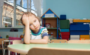 Sad child in kindergarten. Depression girl in nursery school